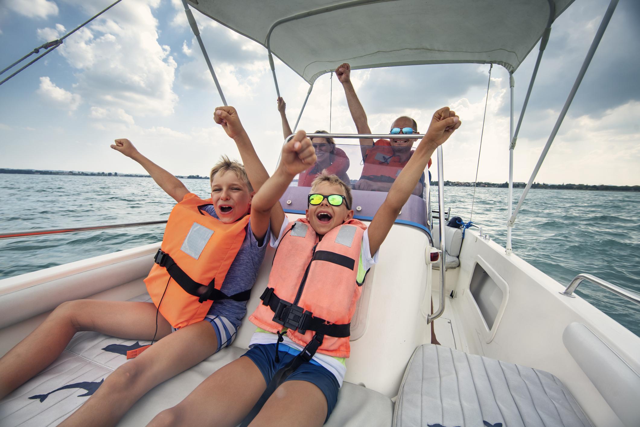 Family enjoying Garda Lake vacations. Parents and kids riding a boat on Lake Garda. Nikon D850